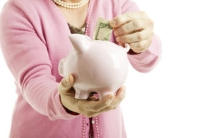 Closeup Of Woman Saving Money In A Piggy Bank White Background