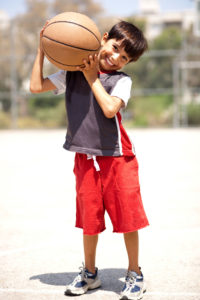 Boy With Basketball On His Shoulders Outdoors