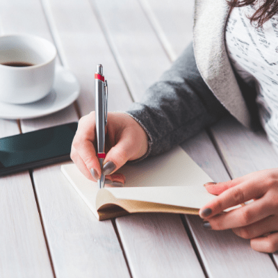 young adult female writing down financial advice in a notebook with coffee