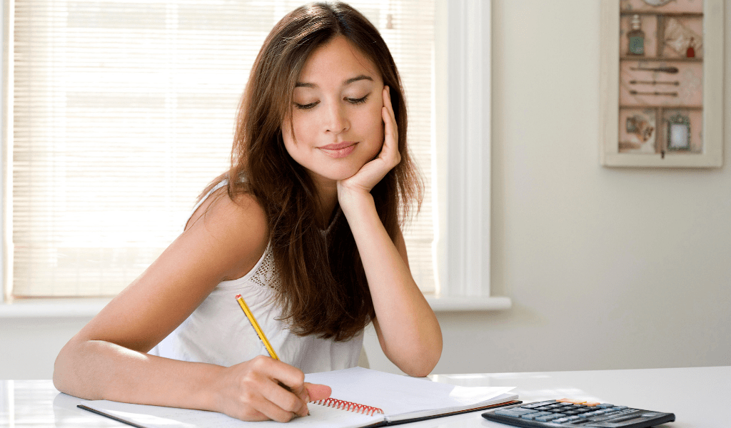 woman writing in notebook and calculator