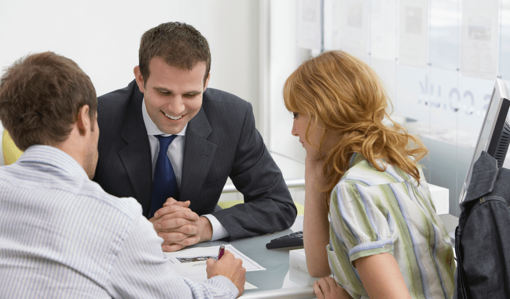 young couple at a bank talking with a young man at a desk
