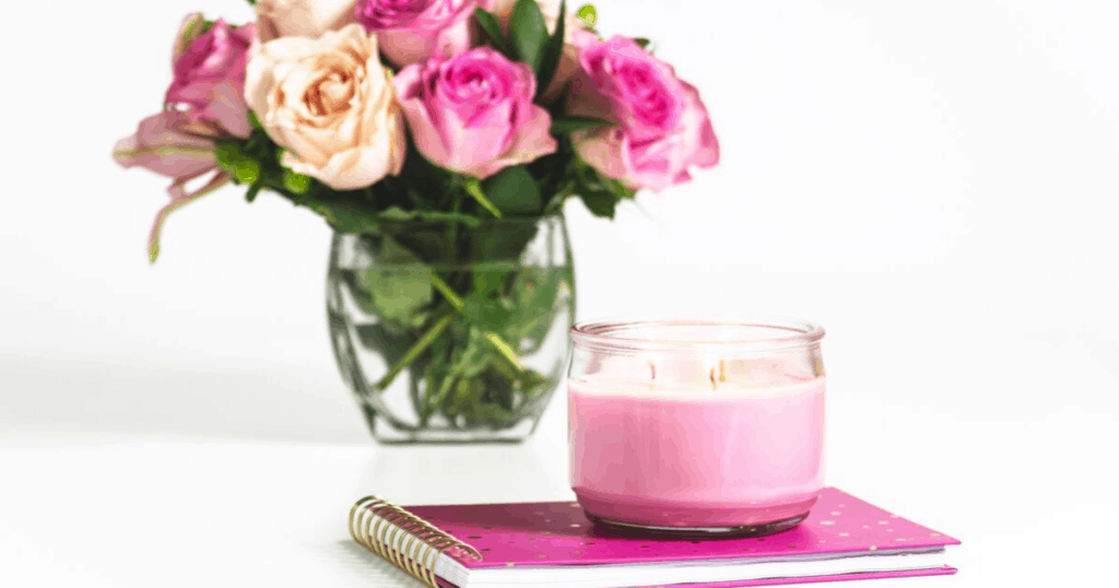 pink flowers in a clear vase, pink notebook and pink candle