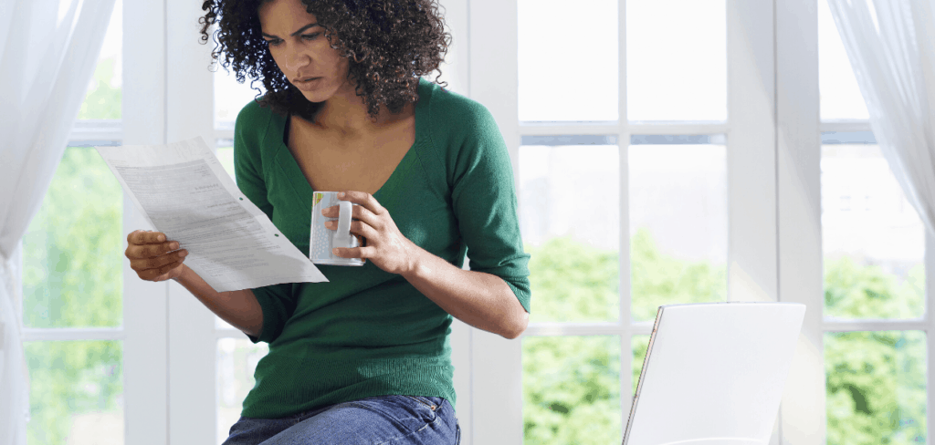 woman looking at collection notice while drinking coffee