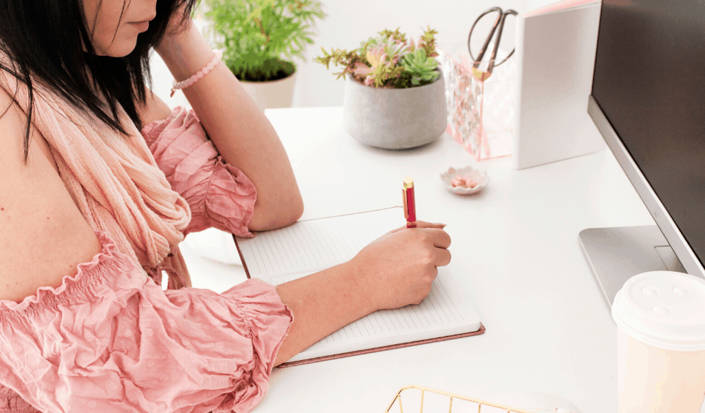 woman at a desk writing in a notebook