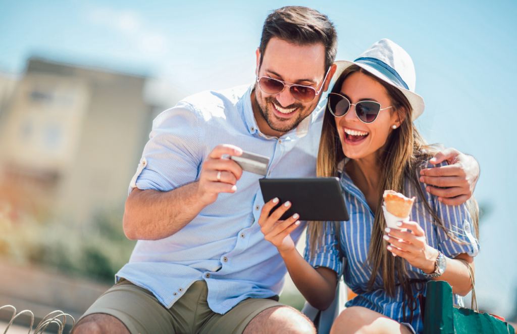 man and woman looking at tablet with  credit card