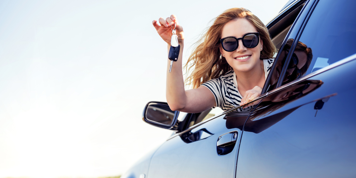 White female holding car keys up while leaning out car window