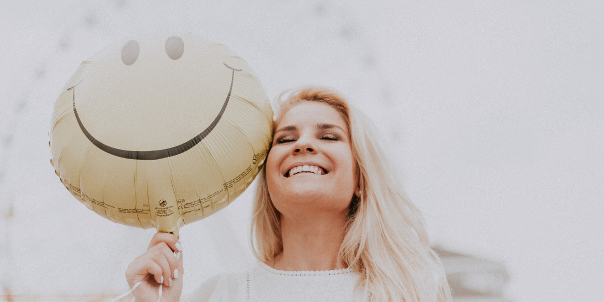 White female smiling while holding a yellow balloon with a smiley face