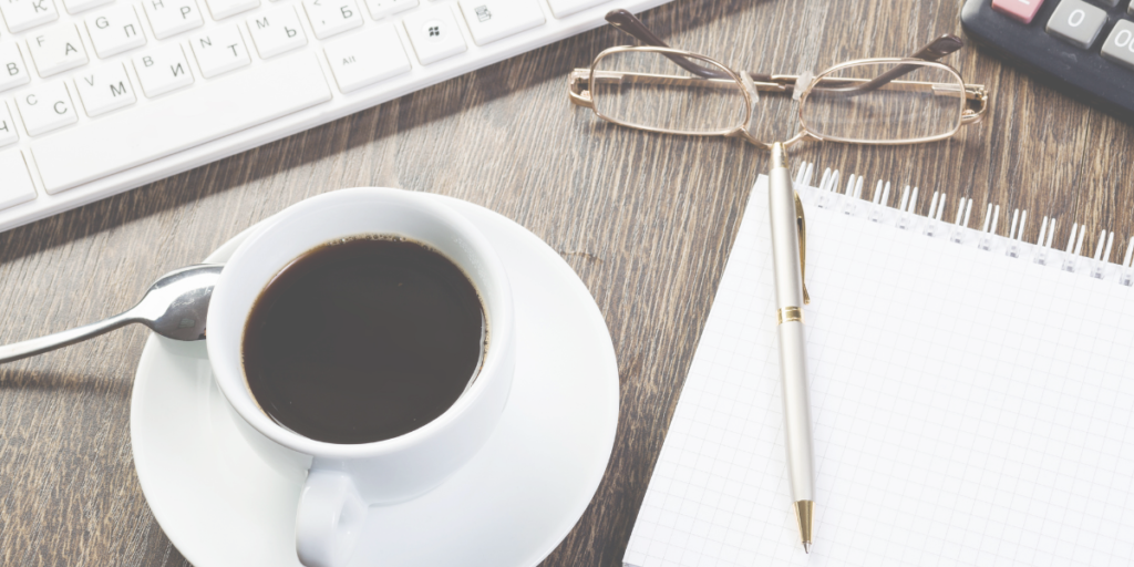 Cup of coffee sitting on a desk with a pair of glasses and pen and notebook sitting next to it