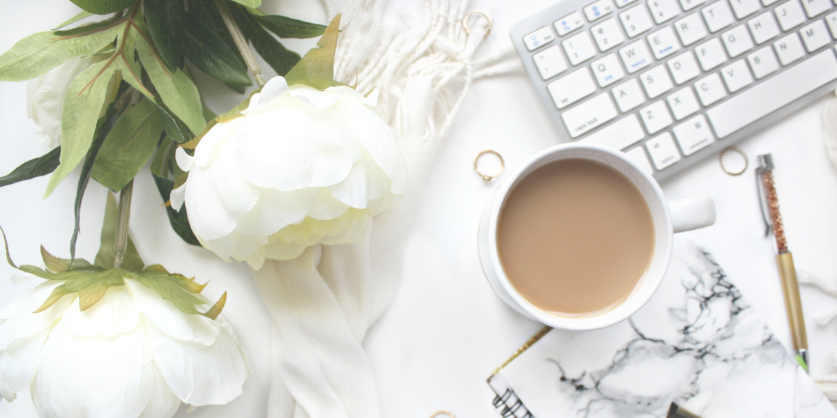 White flowers lying on deask with cup of coffee and a keyboard