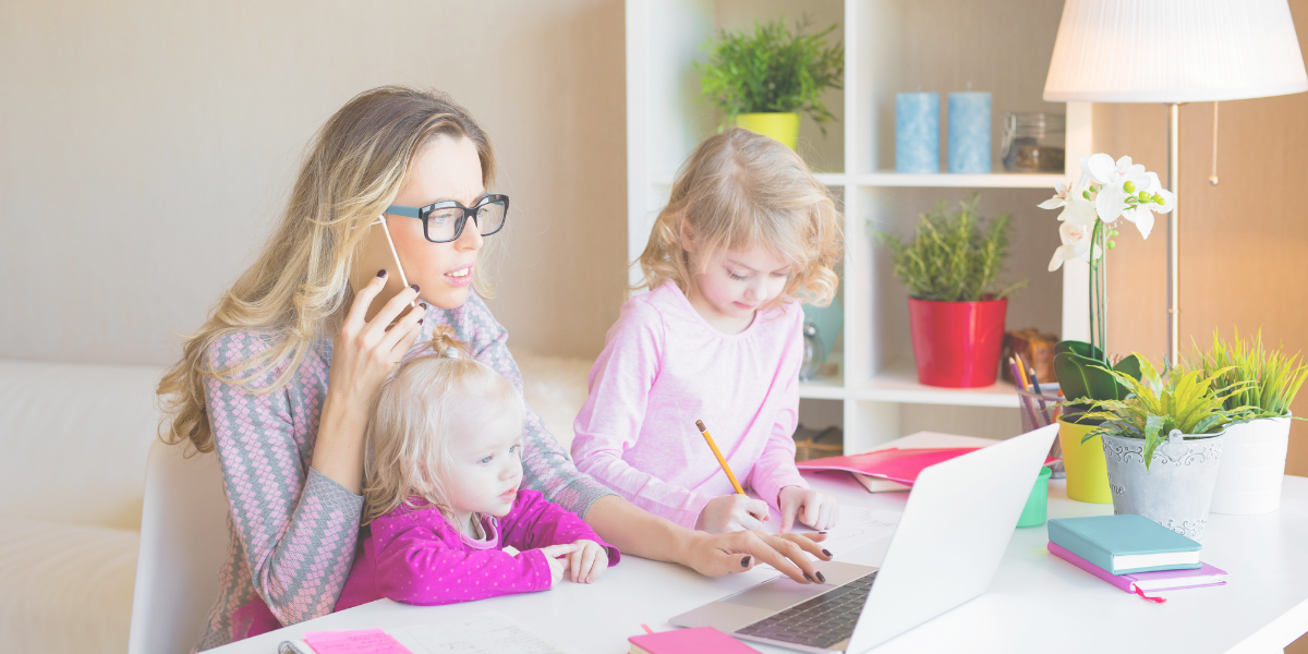 Mother working on her laptop with one small daughter in her lap and another daughter standing next to her drawing on a sheet of paper