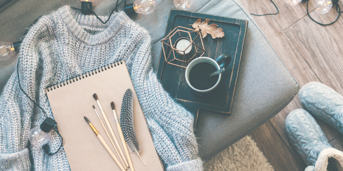 Soft gray sweater lying on an ottoman with a cup of coffee and a notebook