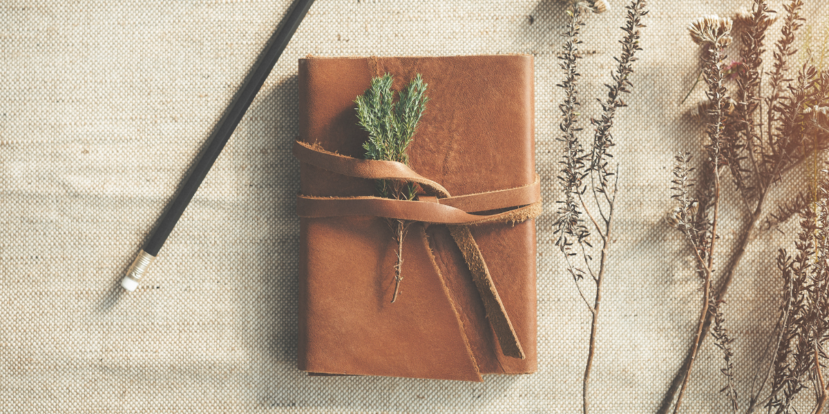 Brown leather journal with wildflowers lying beside it along with a pencil.