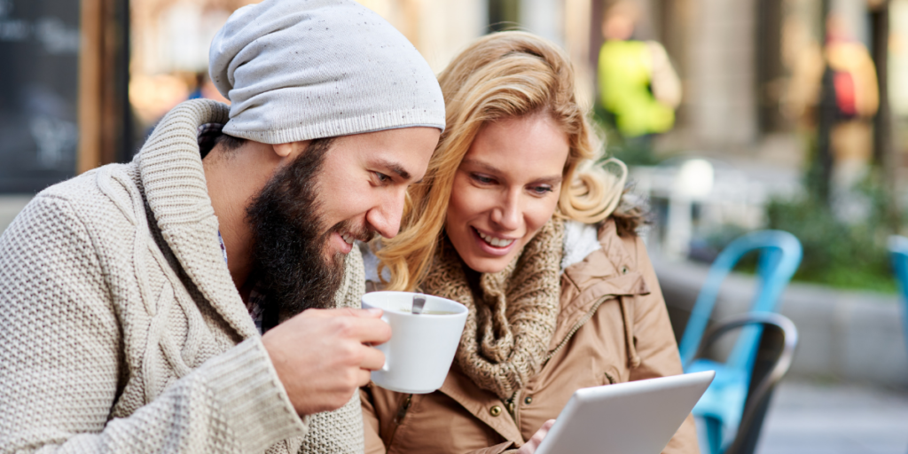 man and woman using free internet outside a coffee shop