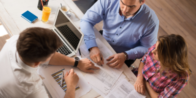 Financial advisor assisting couple with investing their money and earnings to pay off debt.
