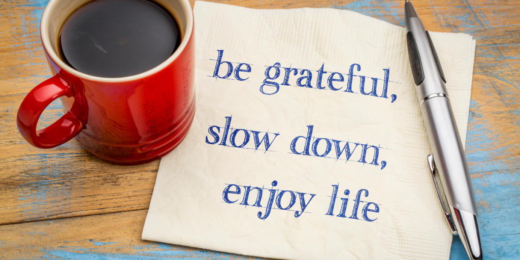 Words of encouragement to be grateful, slow down, enjoy life written on a napkin with a pen and a cup of coffee nearby to change ones money mindset and work towards securing a financial future.