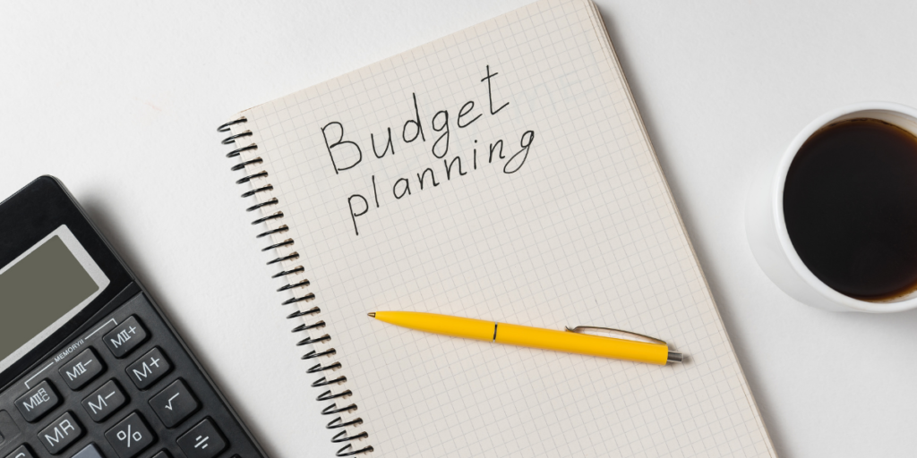 A white notebook with a yellow pen, calculator and coffee on a white desk  with budget planning written on the page with plans to change money mindset and secure a financial future.