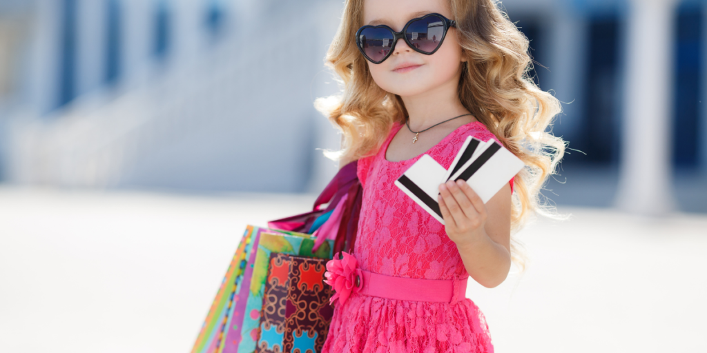 Little girl holding three credit cards and several shopping bags with her mind set on spending money and not worried about finances.