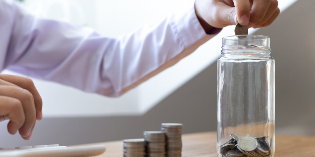 A guy putting money away into a jar because he has changed his money mindset and wants to secure his financial future.