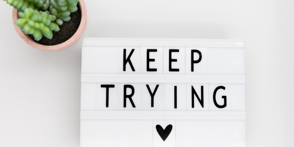 A white sign with a post of keep trying with a heart reminding you to change your money mindset to secure your financial future and if you fail just keep trying.