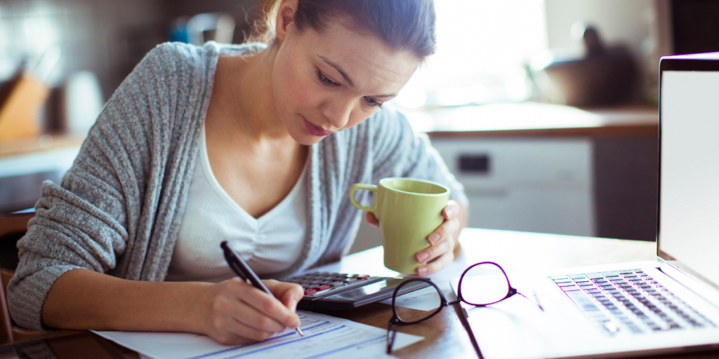 Lady at kitchen table working on budget to pay off minimum payments and investing.