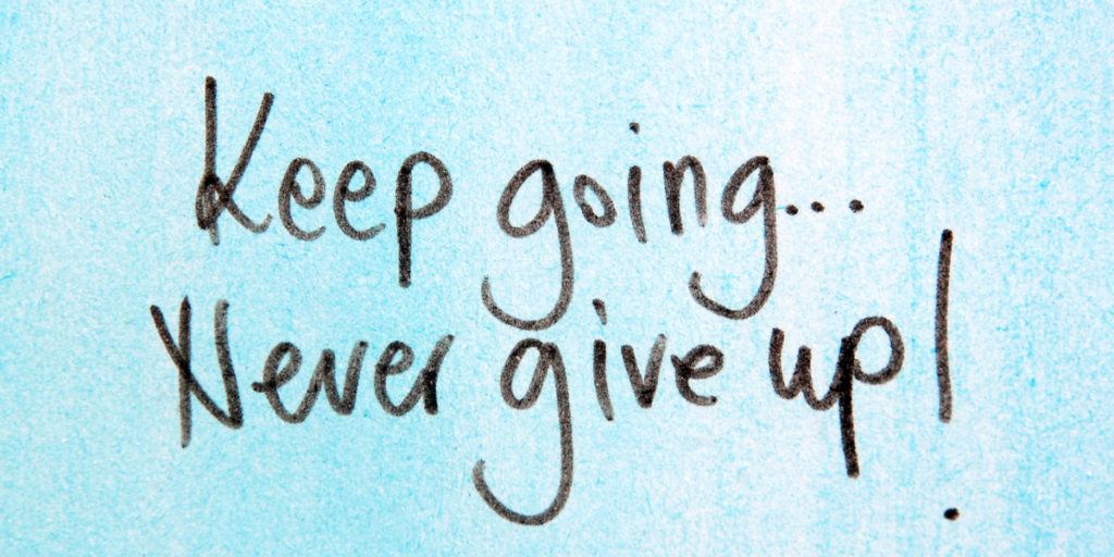 "A light blue background with wording in black markerthat says ""Keep going...Never give up!"" on your financial goals."