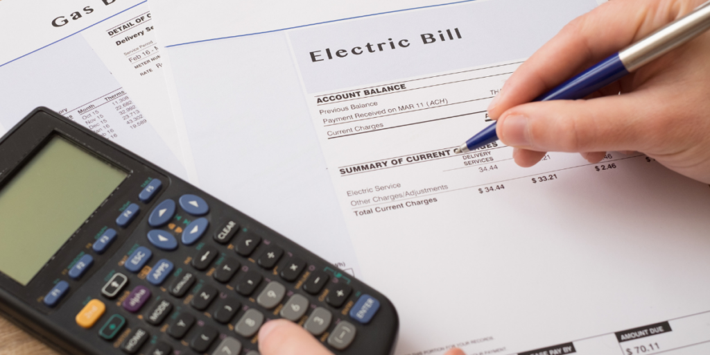 A calculator laying on top of the electric and gas bills with a person holding a pen reviewing the bills in an effort to stick to their budget.