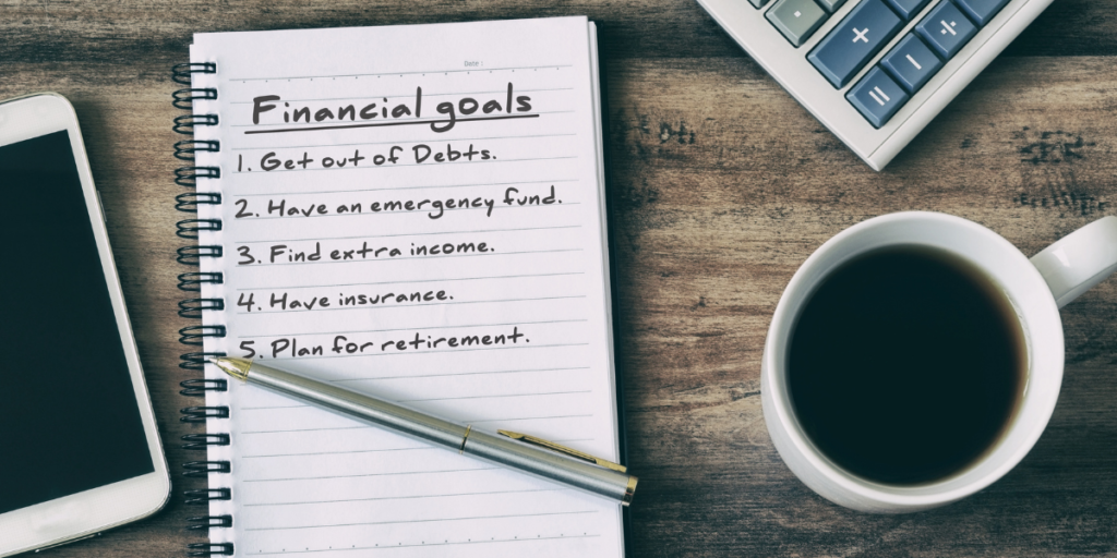 A cellphone, calculator, cup of coffee and a pen on a notepad with financial goals listed 1-5.