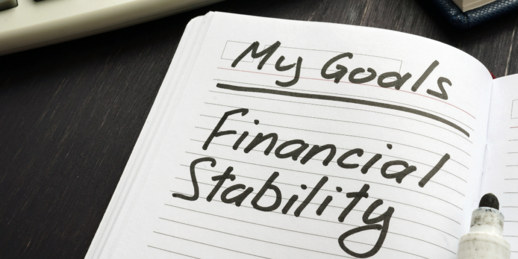 "A notebook and a black marker that was used to write ""My Goals. Financial Stability"" on a piece of paper to reach financial goals."