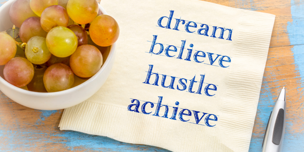 A small bowls of grapes sitting on a napkin with the words dream, believe, hustle, achieve for reaching financial goals.