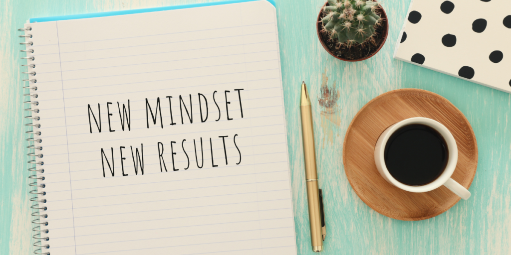 "A notebook on a table with a pen and a cup of coffee with the financial goals wording ""New Mindset New Results"" written on the page."
