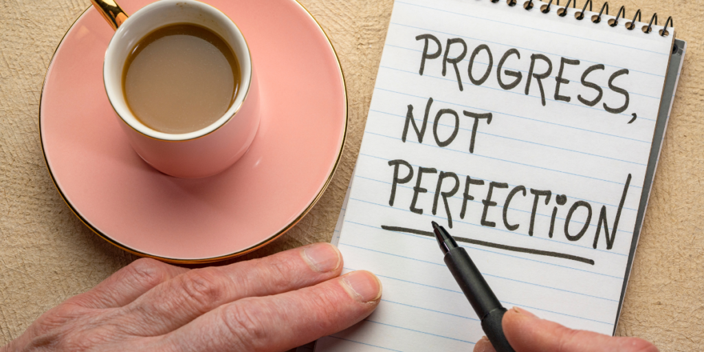 "A person enjoying a cup of coffee with a pen and notepad that says ""Progress, Not Perfection"" reminding us progress is needed in order to reach financial goals."