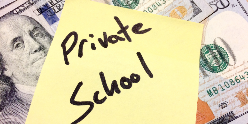 "American money under a yellow post it note labeled ""private school"" reminding one to stick to their budget in order to afford a private school."