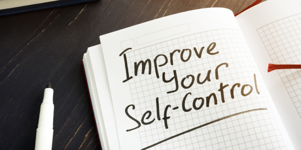 "A grid notebook laying on a tabletop and a marker nearby with ""Improve Your Self-Control"" written on the page as a prompt for one to stick to their budget."