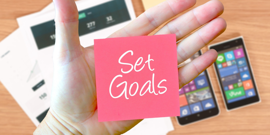 "Cellphones and paperwork laying on a desk with a hand hovering above holding a dark pink post-it note with the words ""set goals"" in white reminding one why they should stick to a budget."