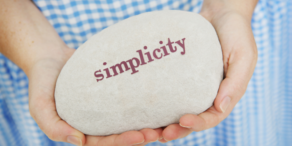 A woman wanting to become a millionaire holding a white rock with the word simplicity.