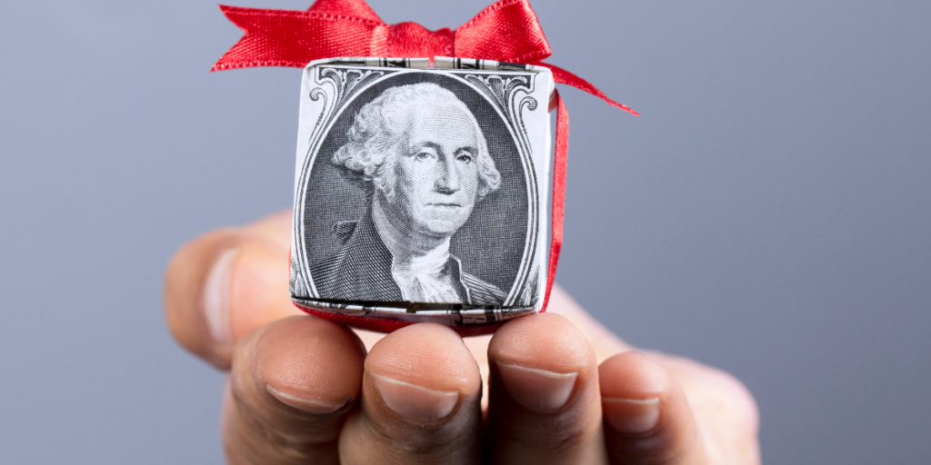 A dollar bill folded into the shape of a gift box with a red bow tied on it.  Money can be a gift when you stick to your budget.