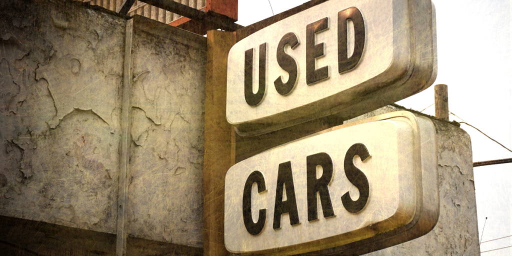 A used cars sign for a car lot to help people buy used cars to help become a millionaire.