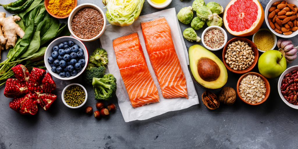 Healthy foods spread out over a table top and a reminder that eating the right and healthy foods can help one have the physical energy to stay motivated.