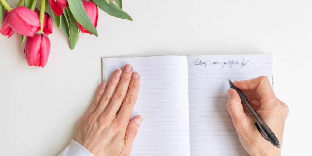 A person writing what they are grateful for in a journal to help them stay motivated.