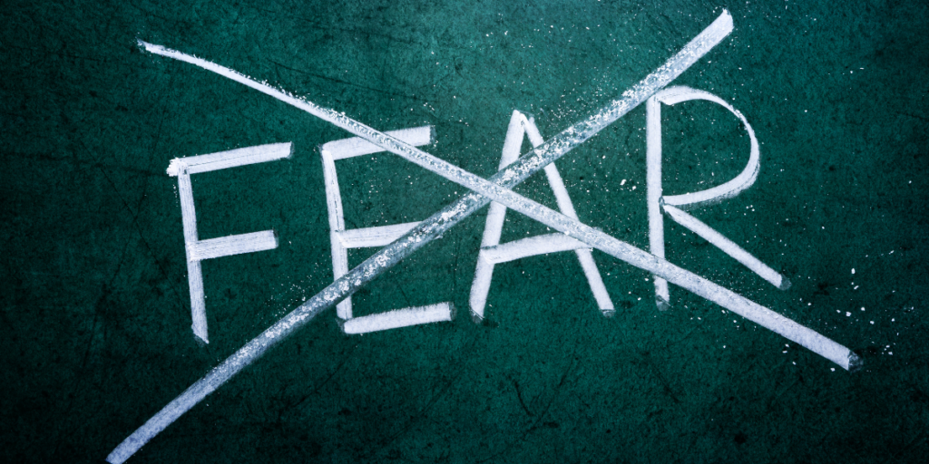 The word FEAR crossed out on a chalkboard.  Don't let fear keep you from staying motivated.