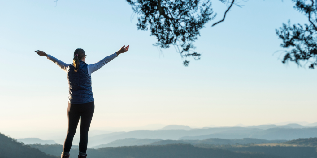 A woman enjoying the view from the top of a mountain because the sky is the limit when you stay motivated.