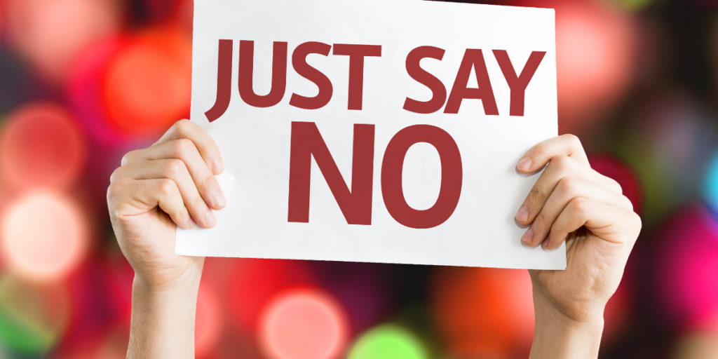 A person holding a sign that says Just Say No to taking on too many commitments in an effort to stay motivated.