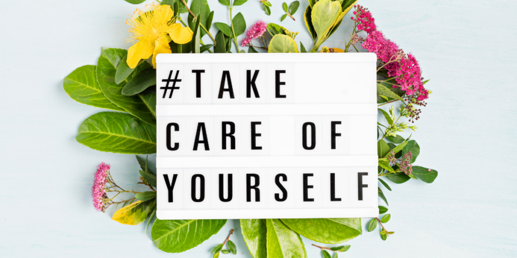 You have to take care of yourself in order to stay motivated. #Take careof yourself on a sign laying on top of a bed of flowers.