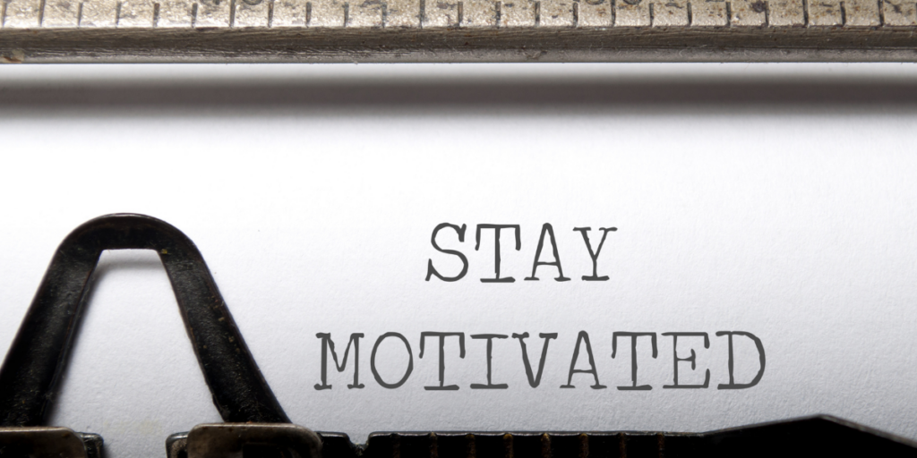 Stay Motivated typed on a piece of paper still in the typewriter reminder the reader to stay motivated on their budgeting journey.