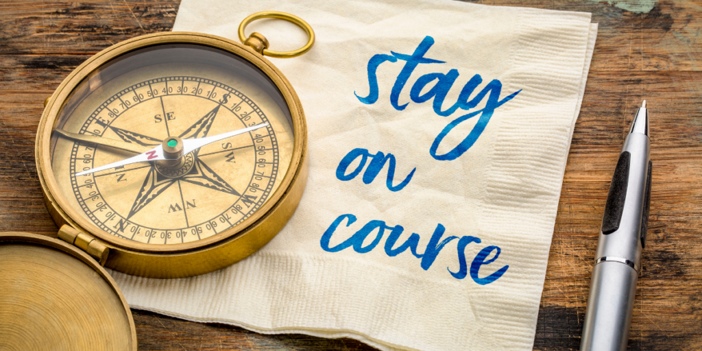 A compass laying on a napkin with the words stay the course on it with a pen nearby and remember to stay motivated.