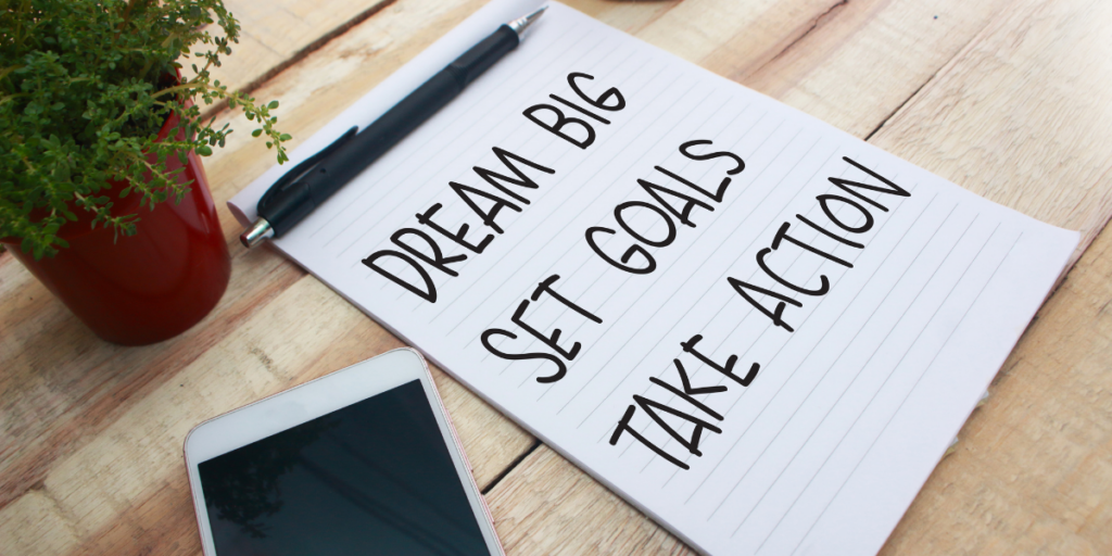 Staying motivated means reminding yourself to Dream Big Set Goals Take Action written on a piece of paper with a pen sitting at the top of the paper and a cellphone near by.