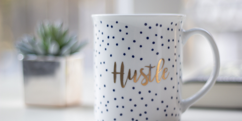 """A white coffee mug with black polka dots with the word """"Hustle"""" in gold lettering reminding us all to keep pushing and take those side hustle opportunities as they come."""