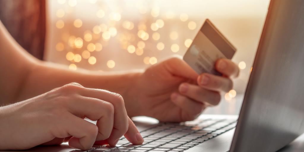 Someone using a laptop holding a debit card earning money thru a side hustle job.