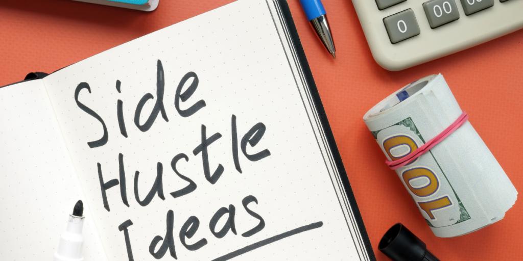 Side Hustle Ideas written on a page of a notebook beside a roll of 100 dollar bills, a pen and a calculator.